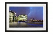 Silhouetted couple look out from More London Riverside to a classic London skyline. Black Frame