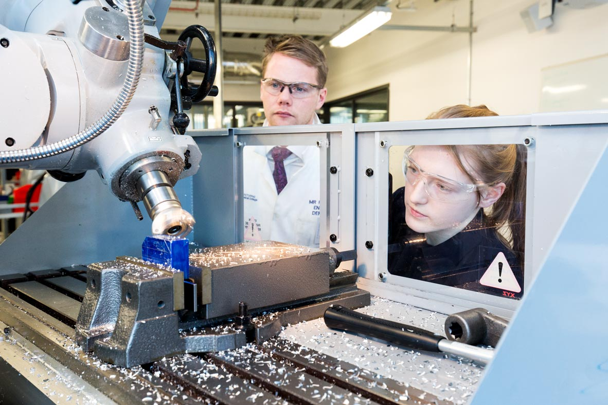 female engineering student working on a milling machine is observed by an instructor