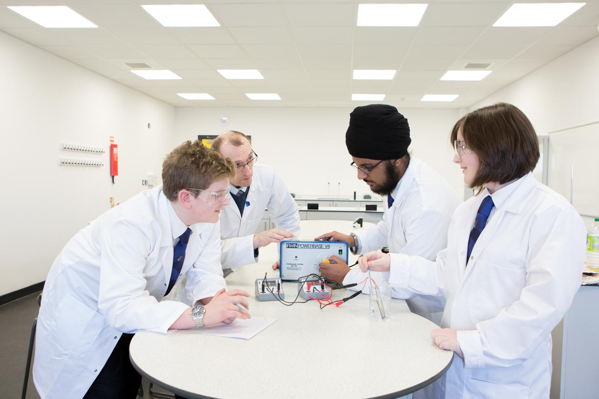 UTC students experimenting in science lab with teacher