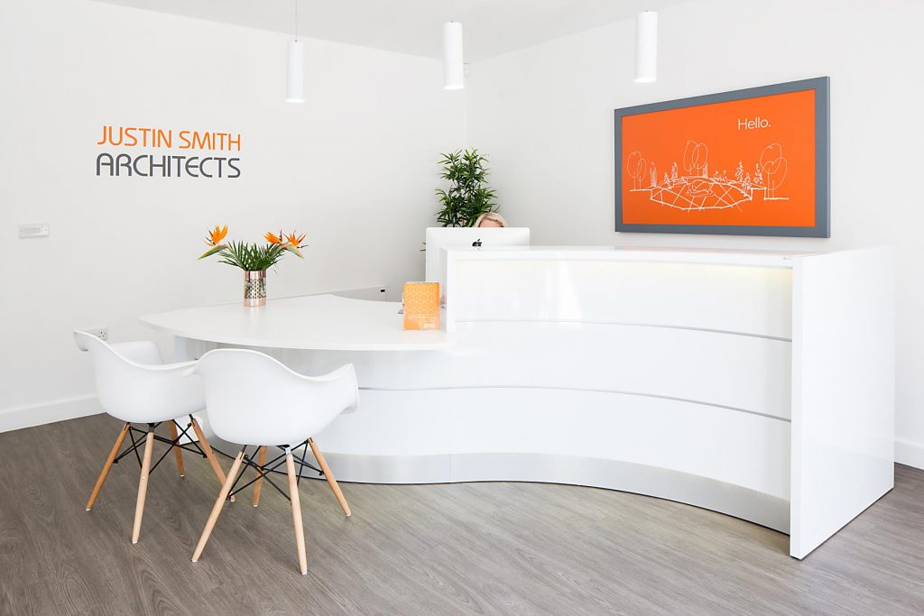 Interior photograph of reception area at architects reception area, colours are white and accent orange