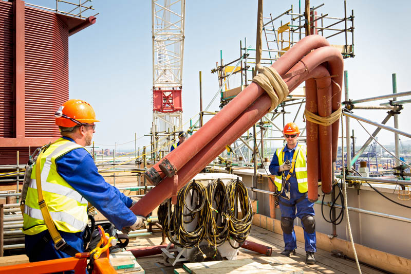 construction workers handling pipe work