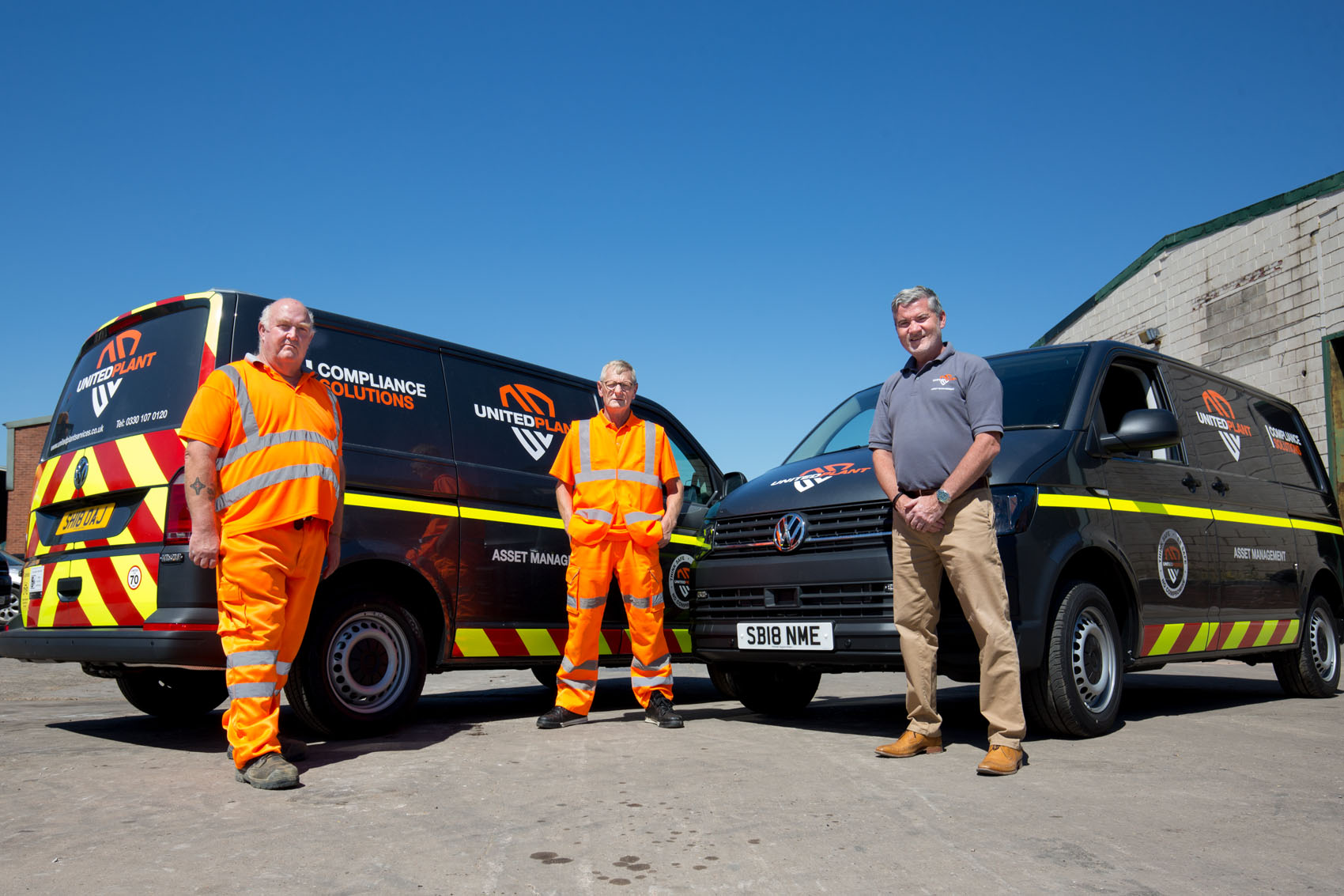 Two enginners in orange overallsand the director in fron of new vans
