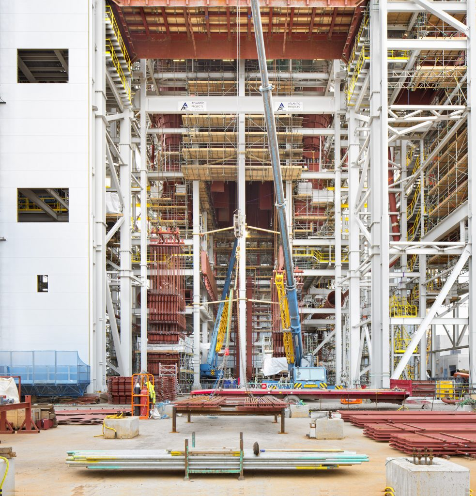 Teesside power plant under construction to cranes in front of steel and pipe work by construction photographer Matthew Jones.