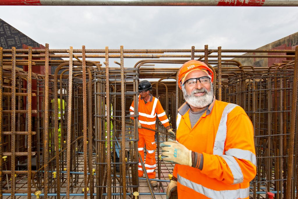 Construction worker wearing orange PPE working on building of steel cage
