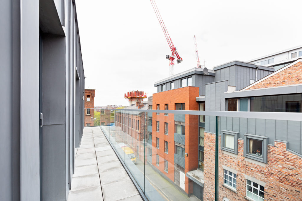 Architectural photograph showing exterior glass balustrade, looking from top floor towards red crane