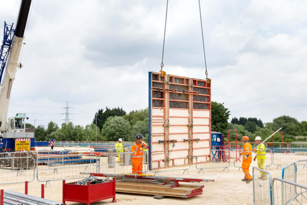 Shot of early construction at a gas plant, four construction workers moving large panels by crane