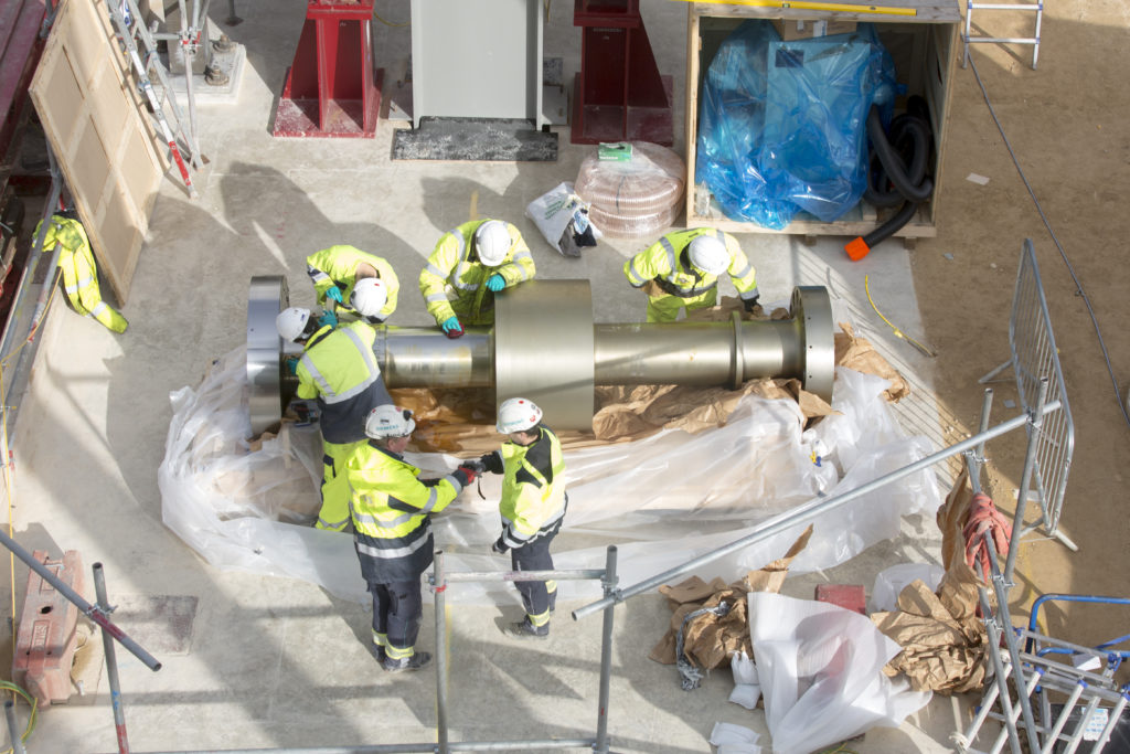 Photographed from above six construction engineers working on a natural gas plant component