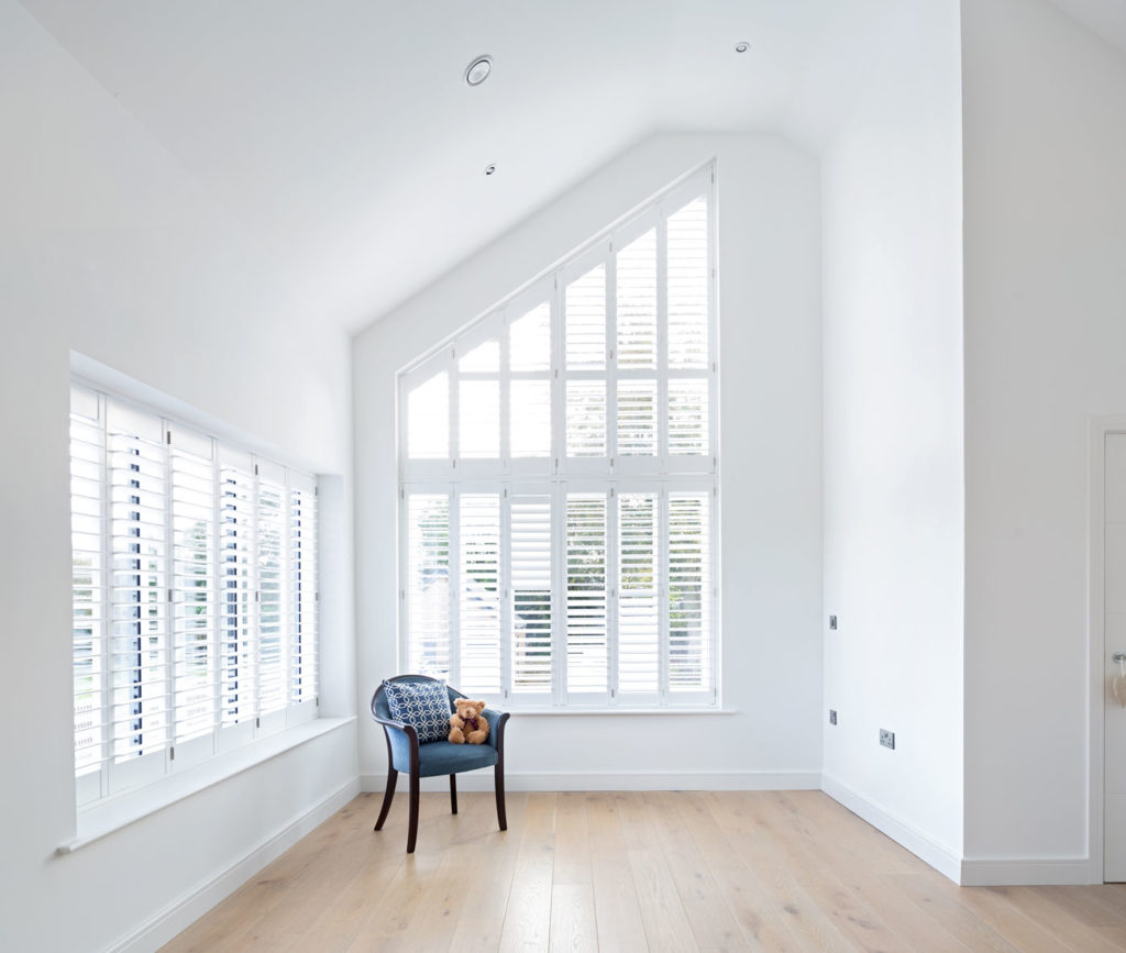Slatted blinds at feature windows in white room with blue chair and seated teddy bear