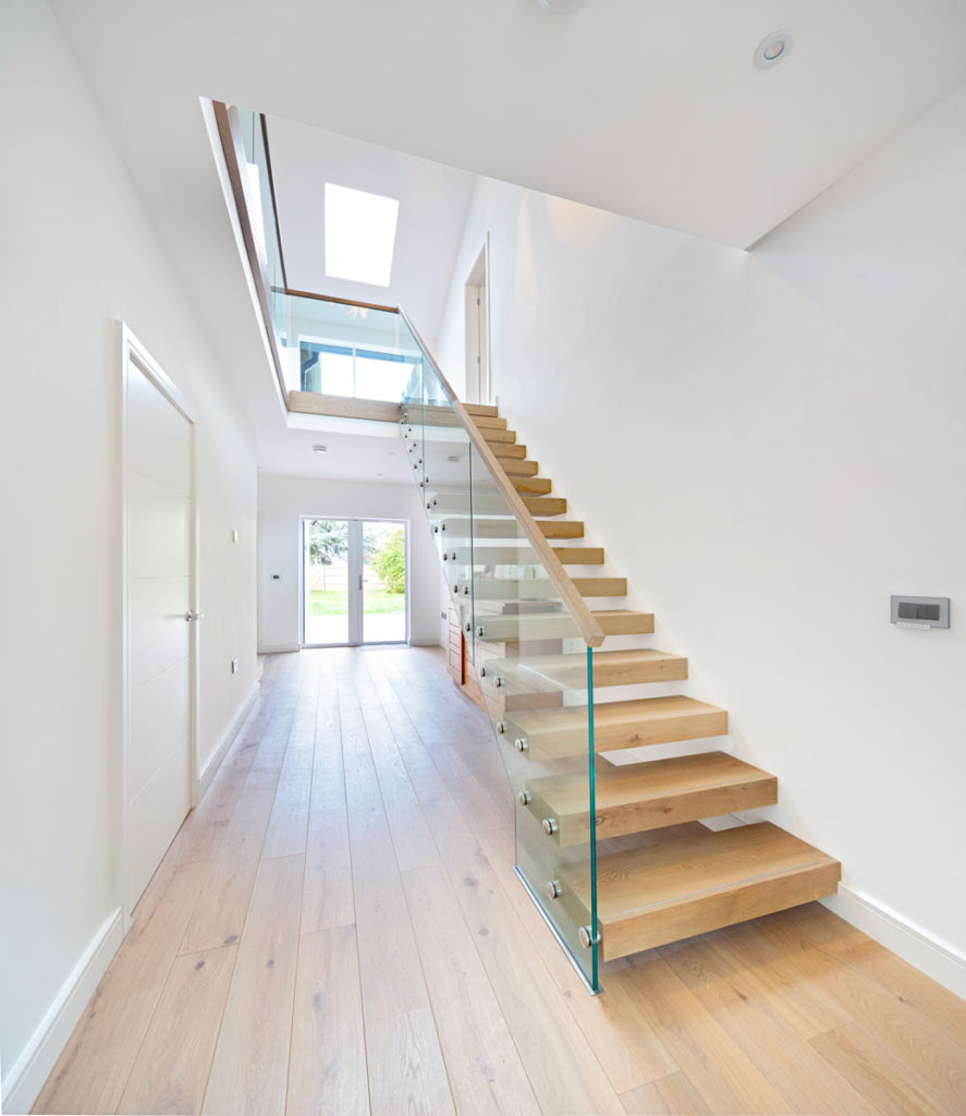 Wood and glass floating staircase in white hallway with view of skylight at top of stairs