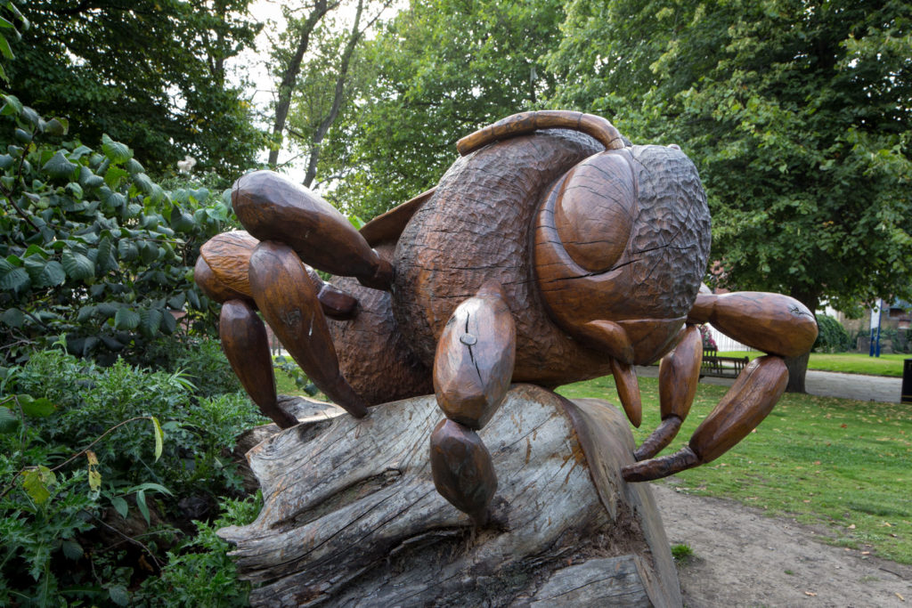 Large wooden bee sculpture on trunk.