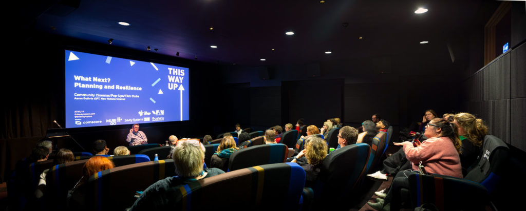 small cinema auditorium, speaker and audience member in conversation