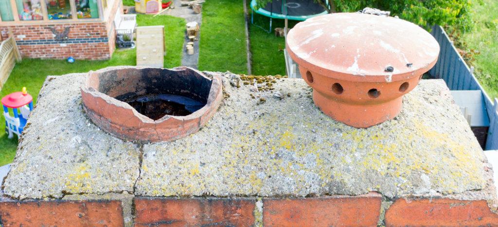 A broken chimney pot on a chimney stack