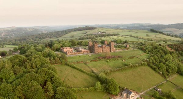 Riber Castle from the air surrounded by green fields and trees incredible Derbyshire countryside