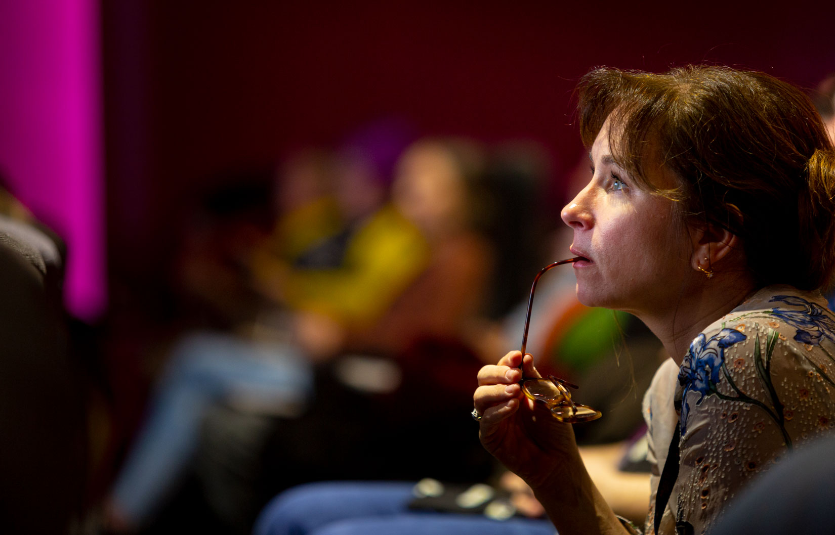Side head and shoulders shot of woman totally absorbed watching film at Broadway Cinema
