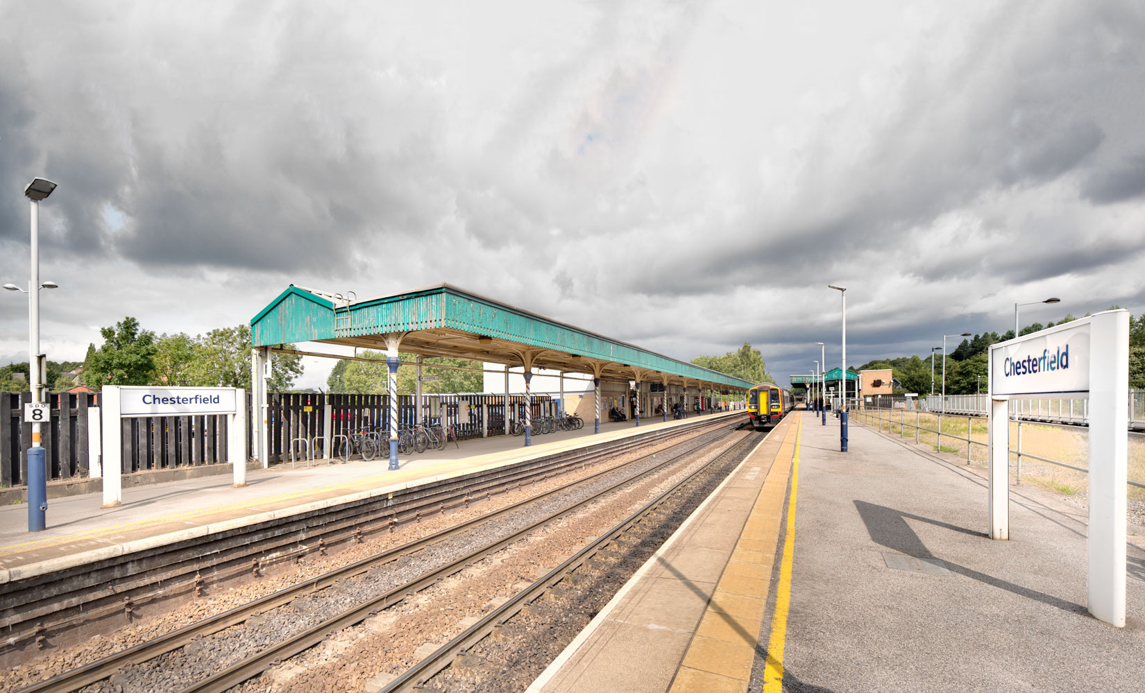 Chesterfield Train Station looking down towards the green roofed platform with train coming towards you