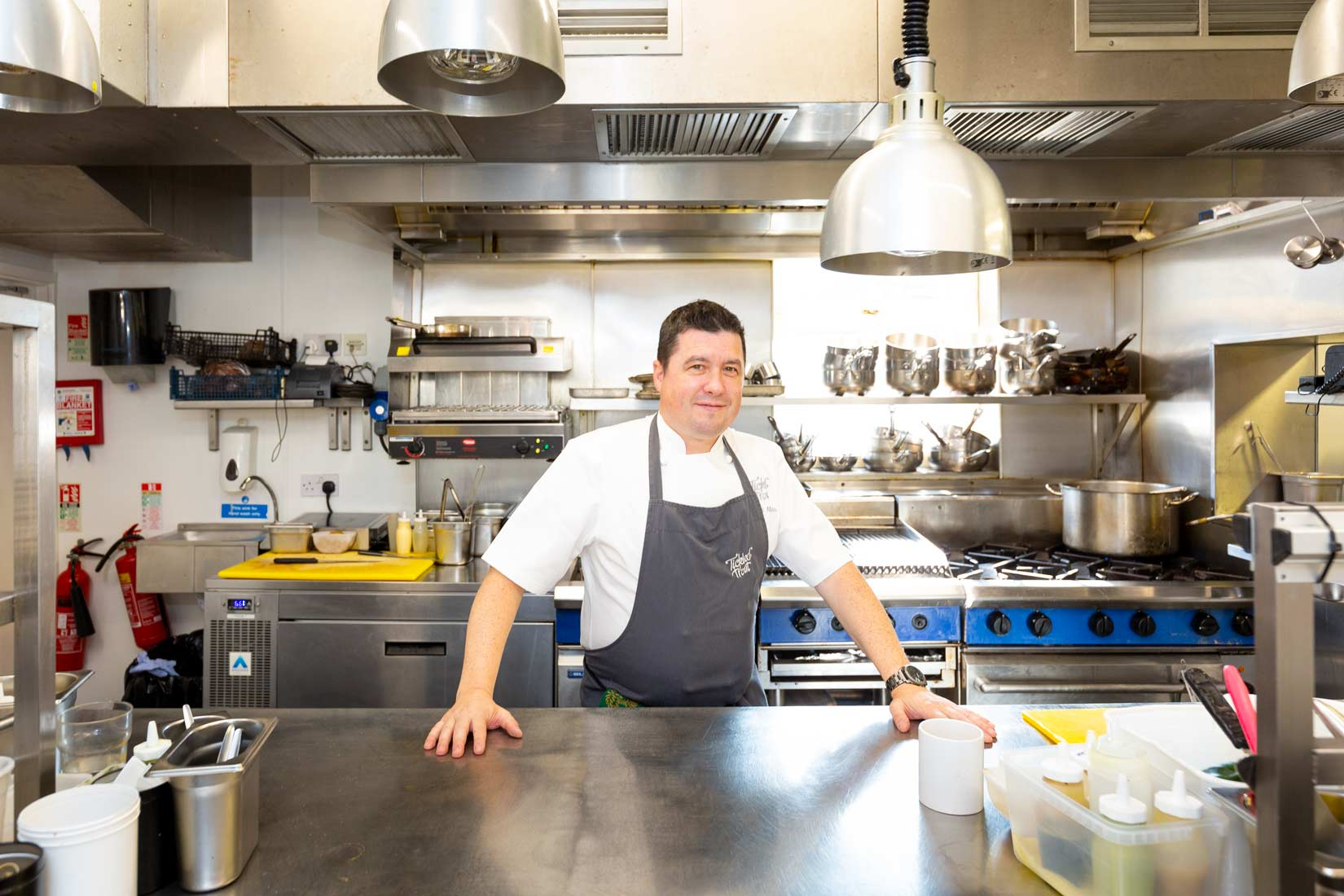 Portrait photography of chef standing over a stainless steel table