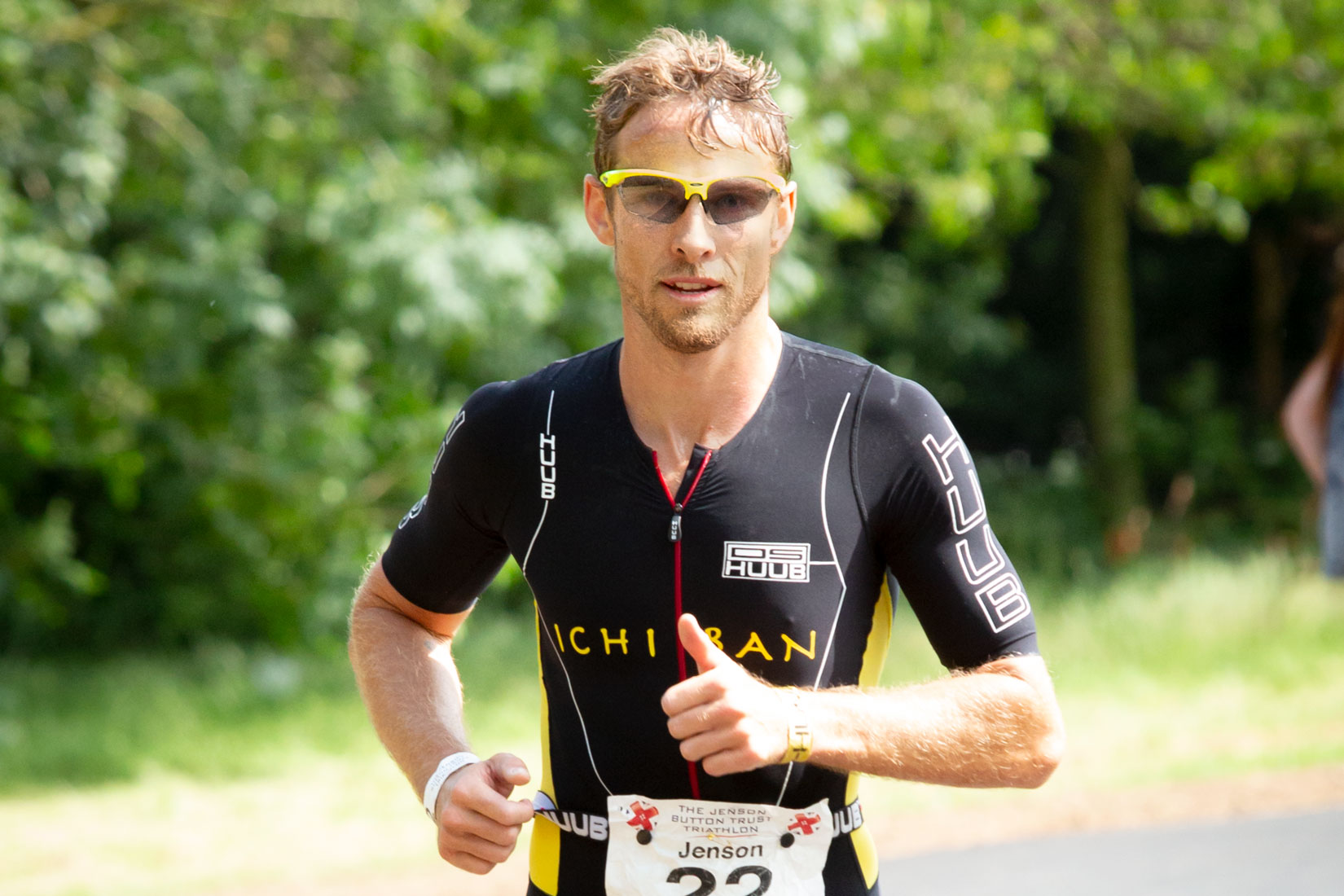 Jenson button with thumb up running in Derby Triathlon