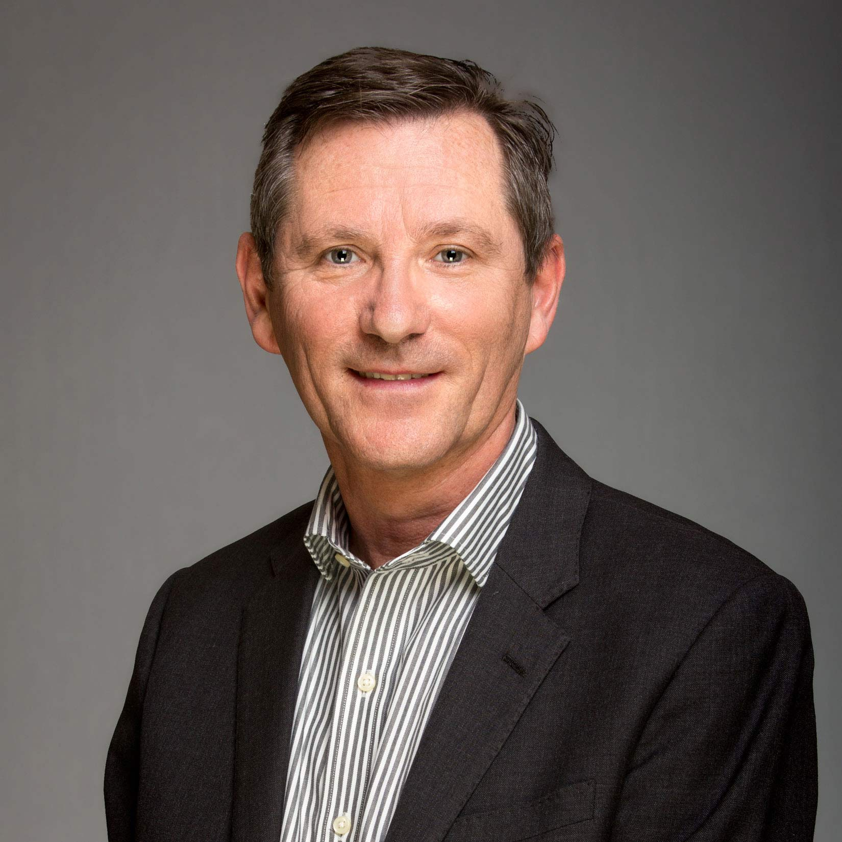 Headshot of businessman with shirt and jacket against a grey background taken for his Linkedin Profile