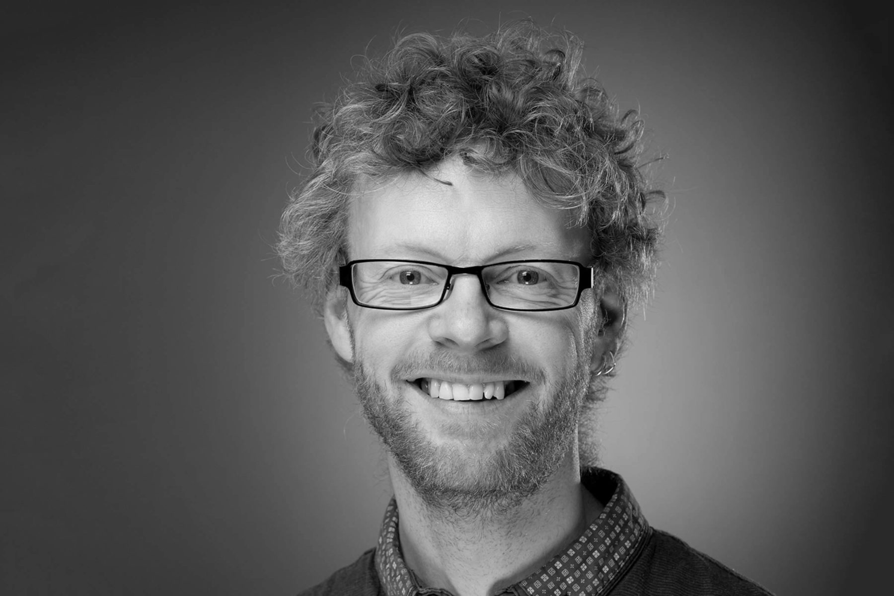 Black and white portrait headshot of man smiling with glasses beard curly hair