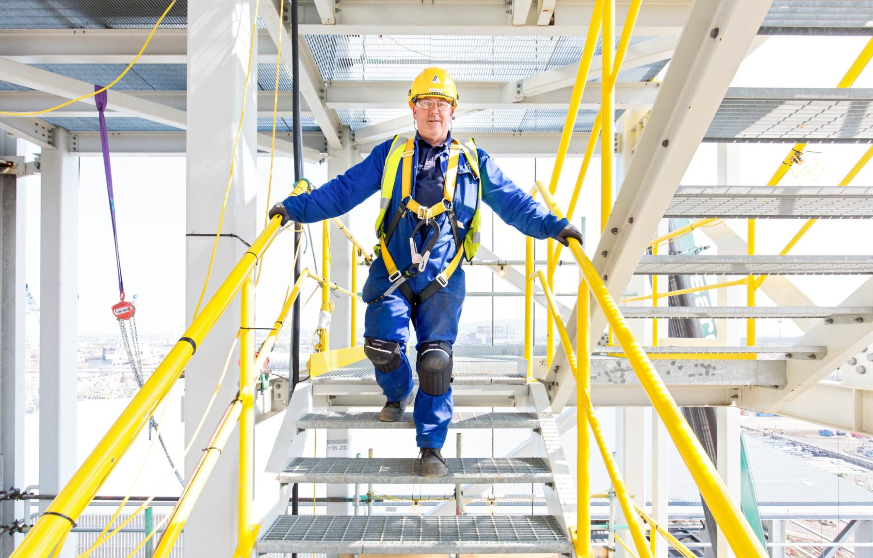 Construction worker in blue overalls wearing yellow hat and safety harness, standing on stairs with yellow rails