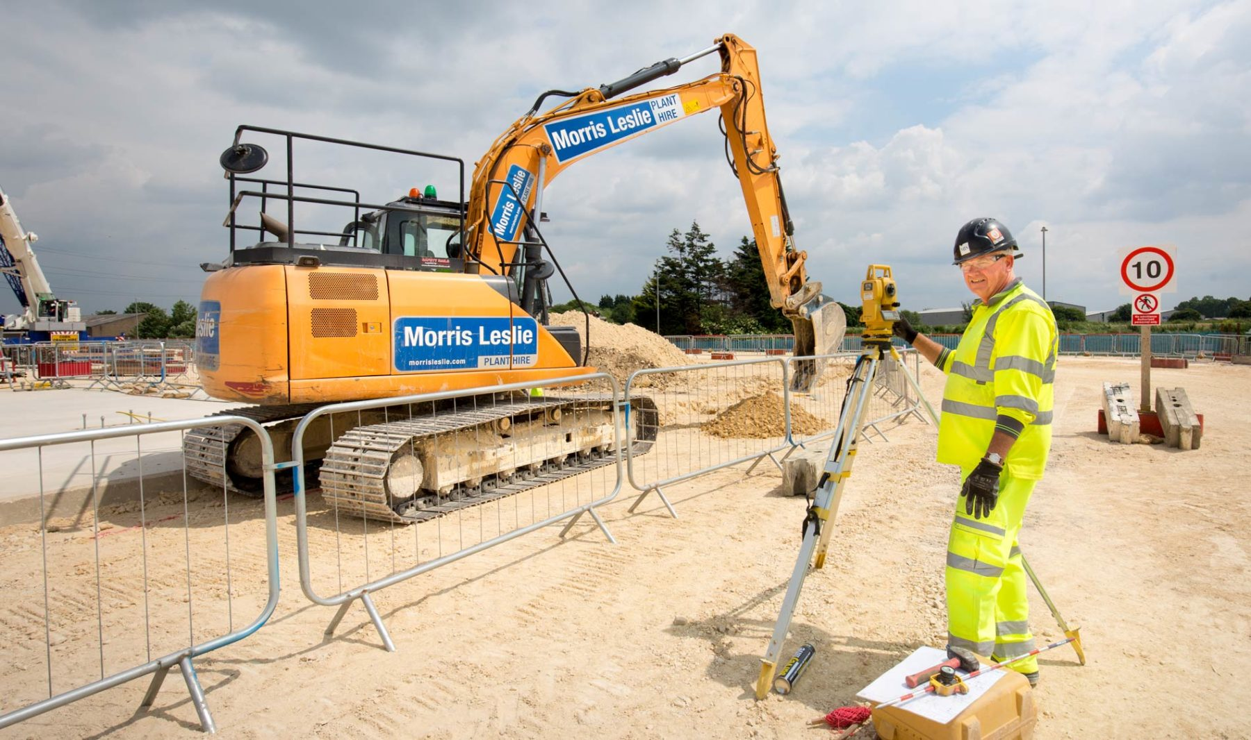 Excavator on site with surveyor and theodolite starting foundation work