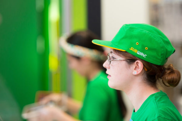 Close up sideways on head shot of woman in green uniform and cap working at the 'Subway' food chain store