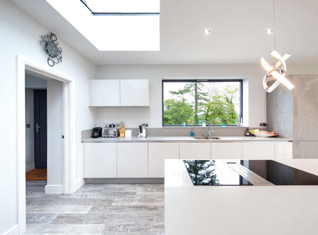 Architectural Interior large white kitchen with island and large skylight, looking towards plain glass picture window