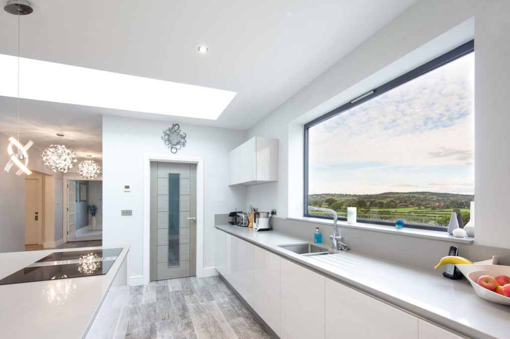 Architectural Interior large white kitchen looking across field through plain glass picture window by interior photographer Matthew Jones