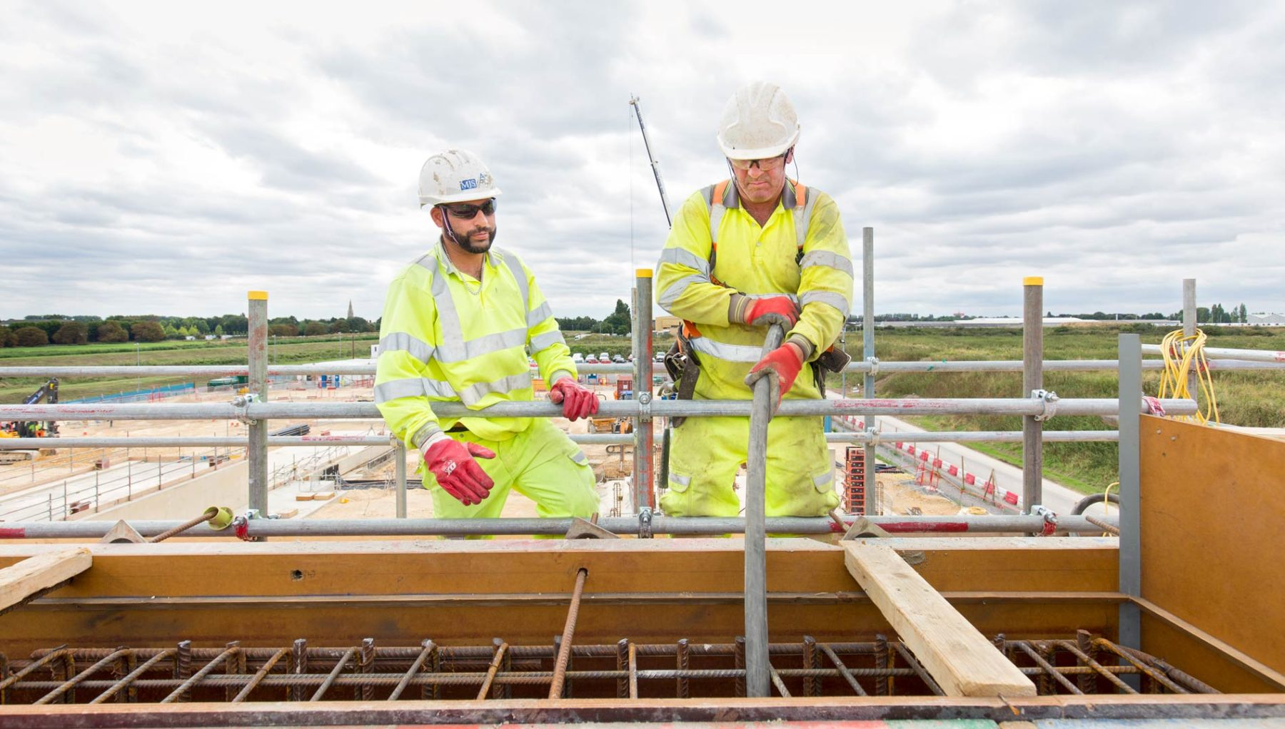 Two construction site workers in yellow high viz poring concrete to blast wall construction