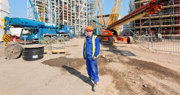 Full length portrait of construction worker in blue overalls on site in front of Sarens Crane