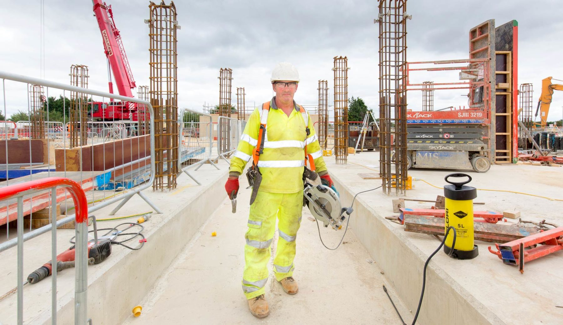 Corporate full length portrait of construction site worker holding a sthil saw