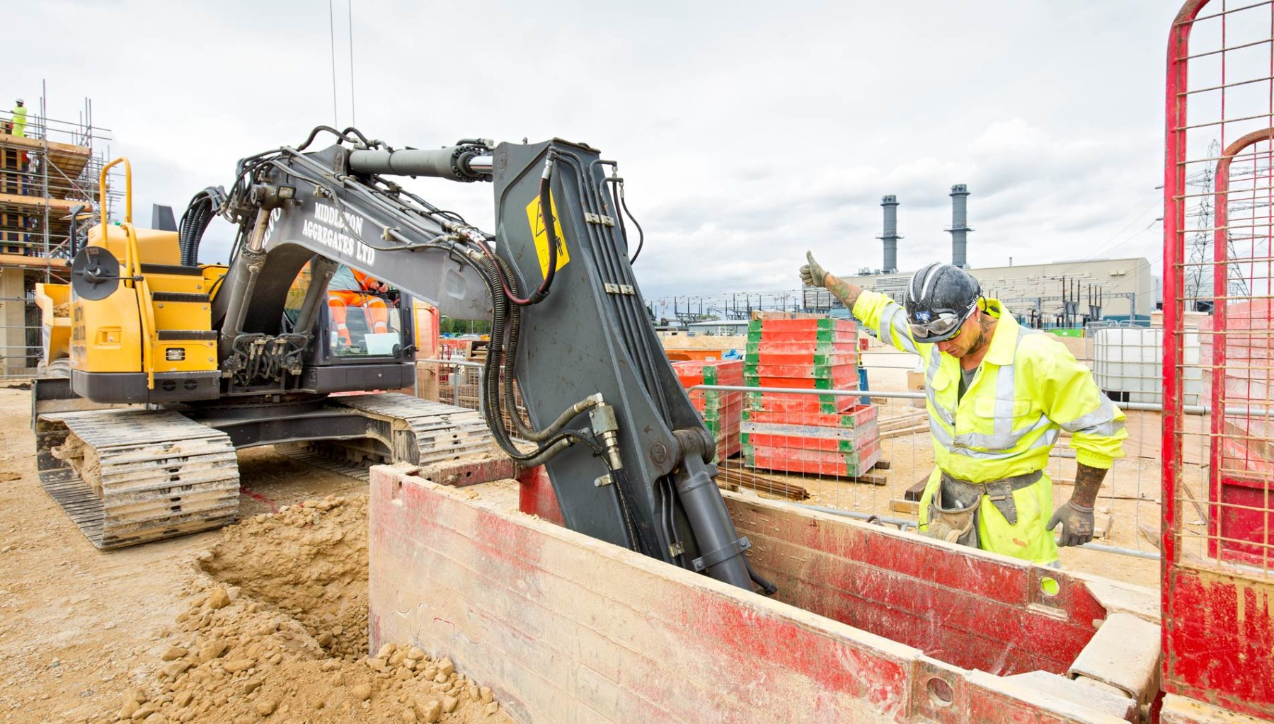 Thumbs up from construction worker to excavator working down metal shuttering