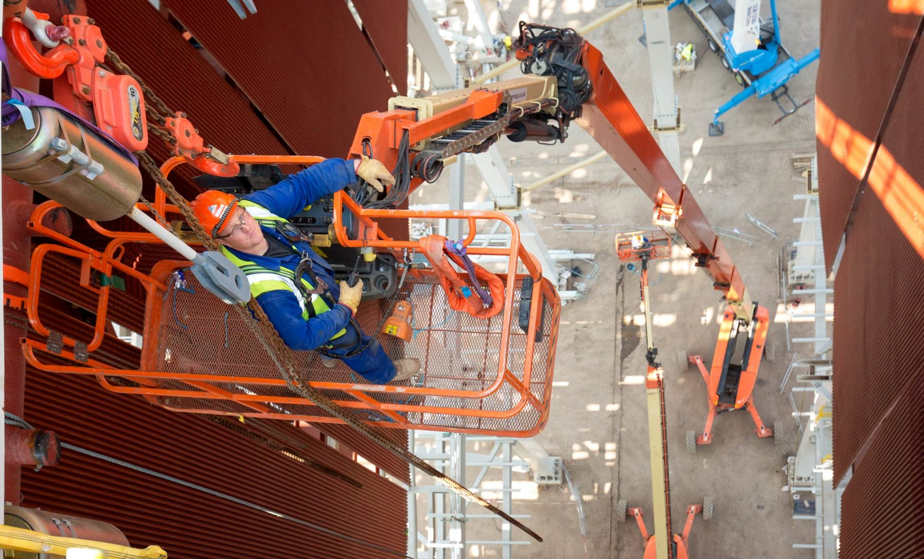Looking down at man in orange lifting cage at great on construction site