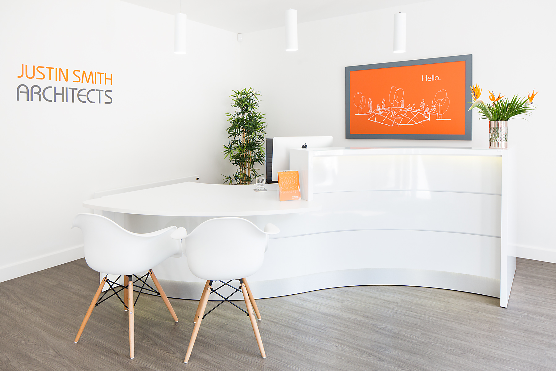 Architect office all white and gloss with bright orange sign behind desk saying 'hello' JSA by interior photographer Matthew Jones