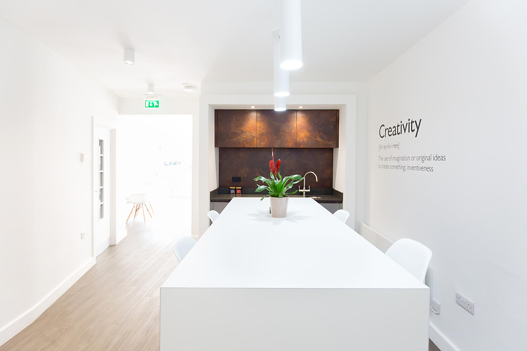 Interior of Architects Boardroom, pure white with copper end wall cupboards and 'creativity' decal on wall