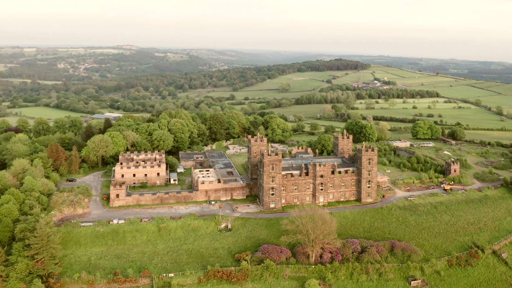 Riber Castle drone shot from above early evening with Crich stand visible in the background