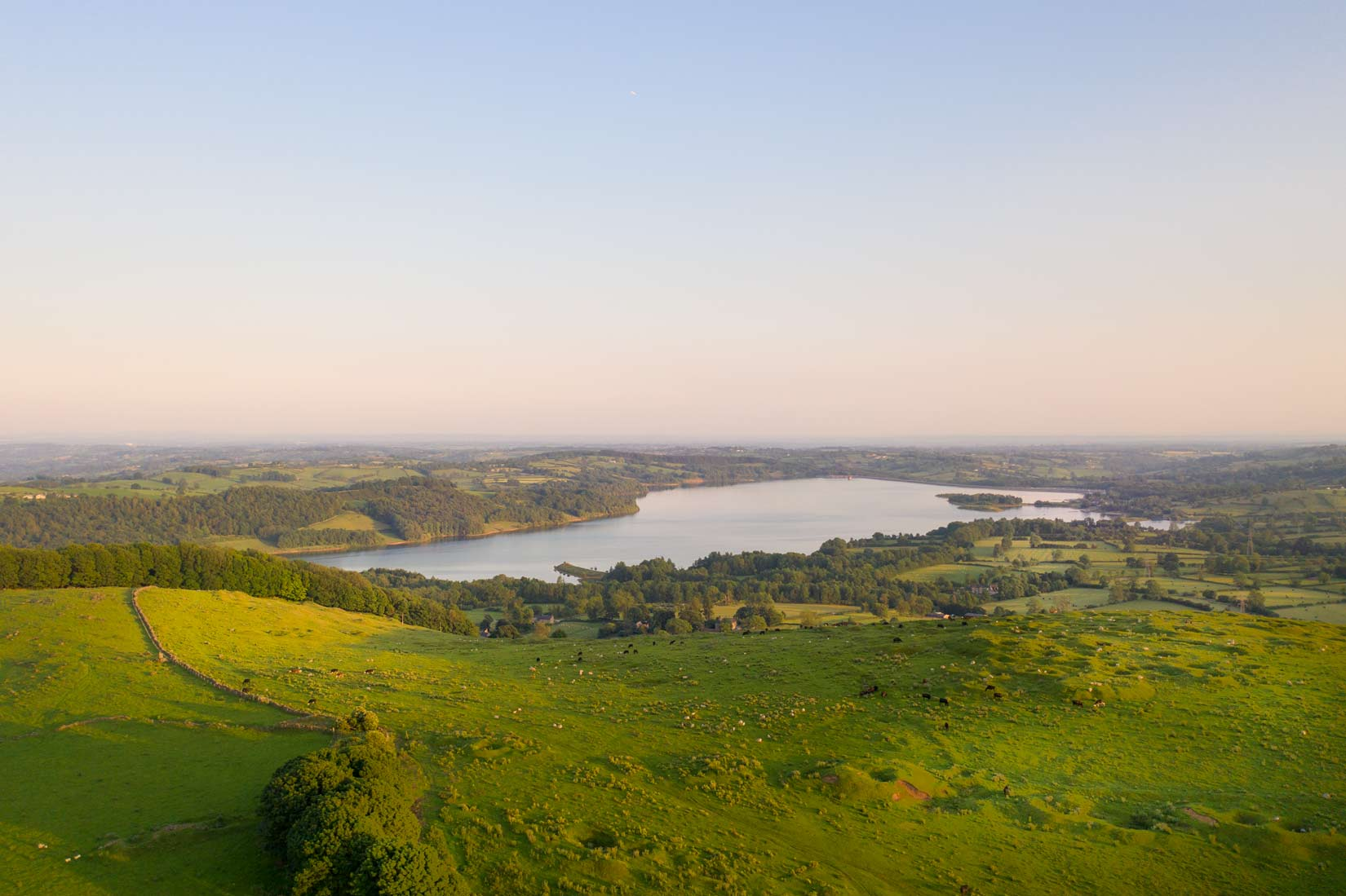 Drone view looking from the wind turibines over Carsington Water towards Derby. Early evening shot with warm hue